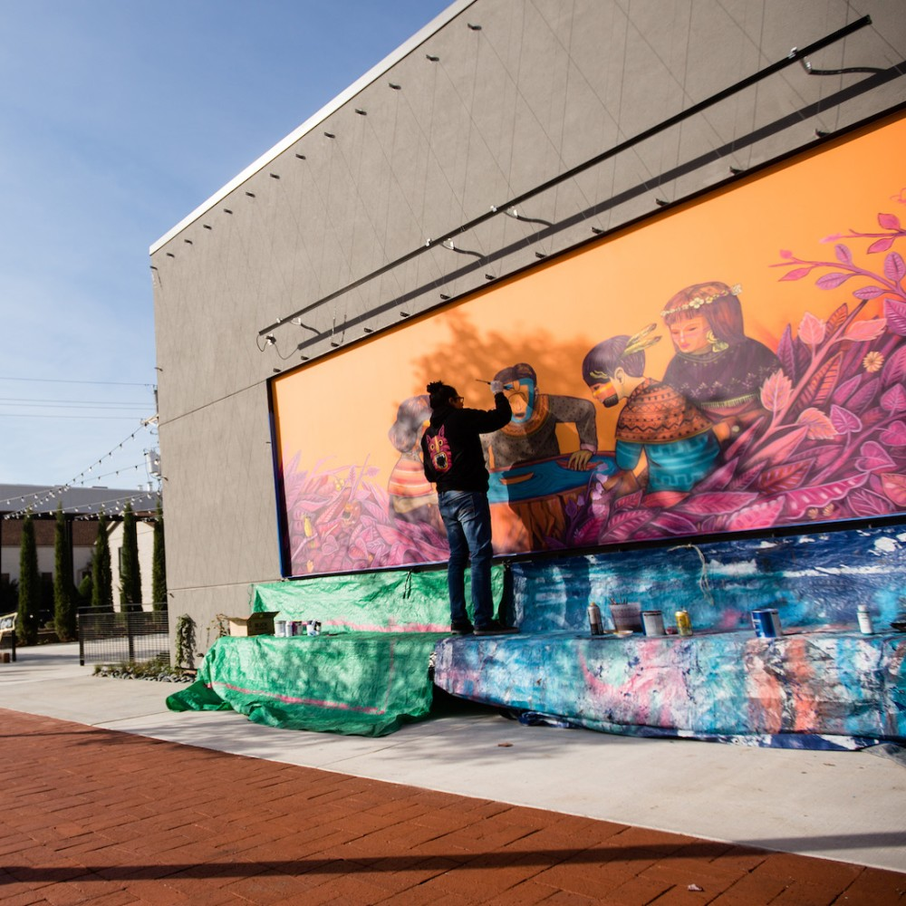 Artist painting a mural in Bentonville 1920x1080