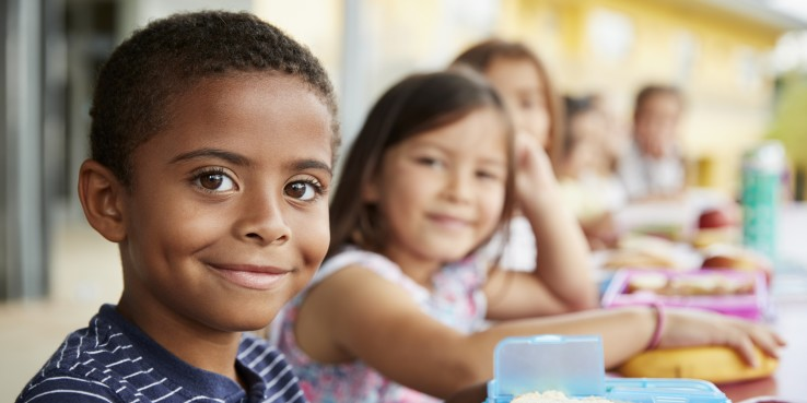 Diverse elementary students having lunch at school