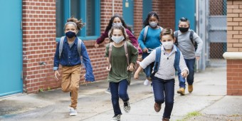 Students with face masks running outside school building